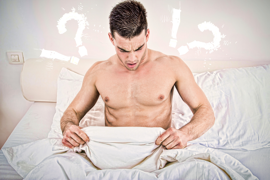 surprised half naked young man in bed looking down at his underwear at his penis under white covers sheet in badroom. Concept photo of male sexuality and man sex problems domestic atmosphere.