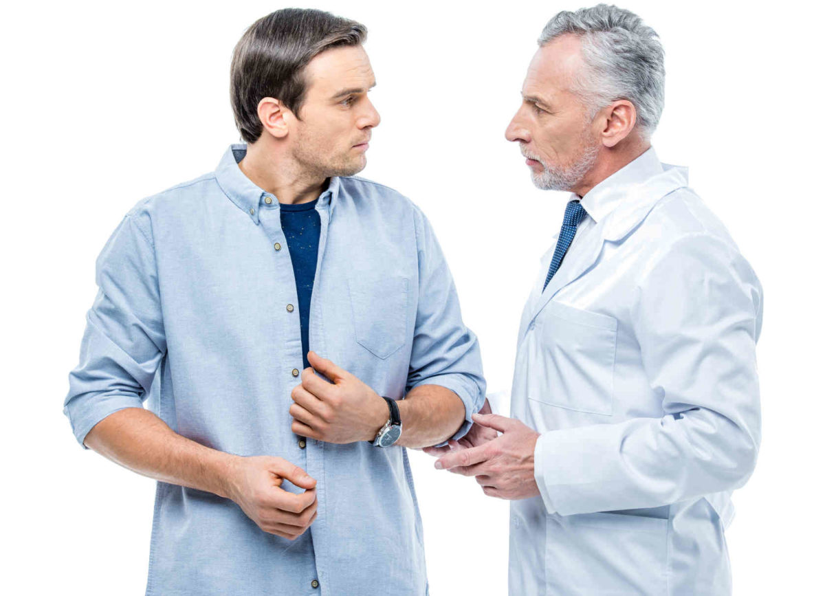 Mature male doctor chatting with patient on white